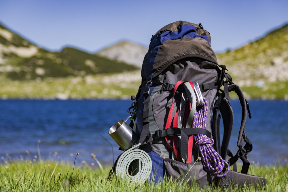 a bag full of hiking and camping gear near the edge of a lake