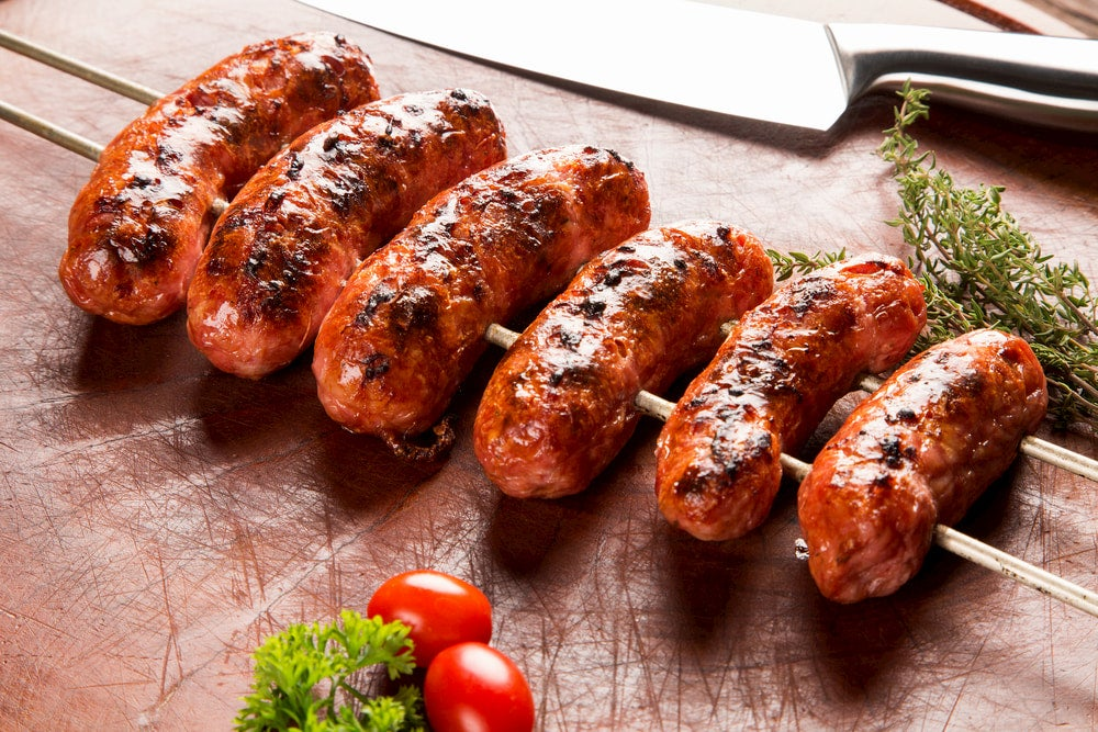 Bratwurst on skewers with garnish.
