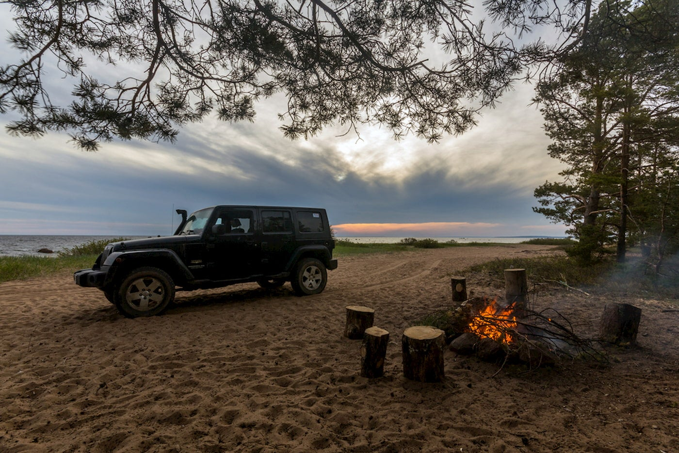 Jeep wrangler parked on beach beside fire.
