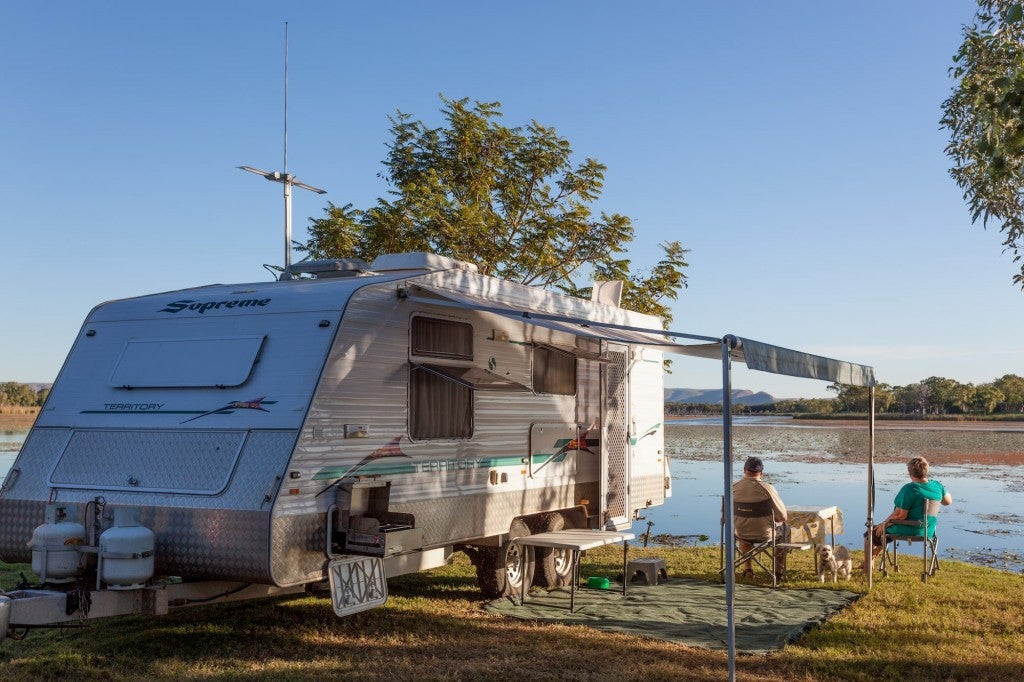 an elderly couple relaxing next to their RV camper near a lake