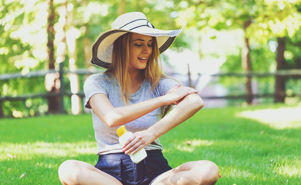 Woman in a park applying sunscreen to her arm