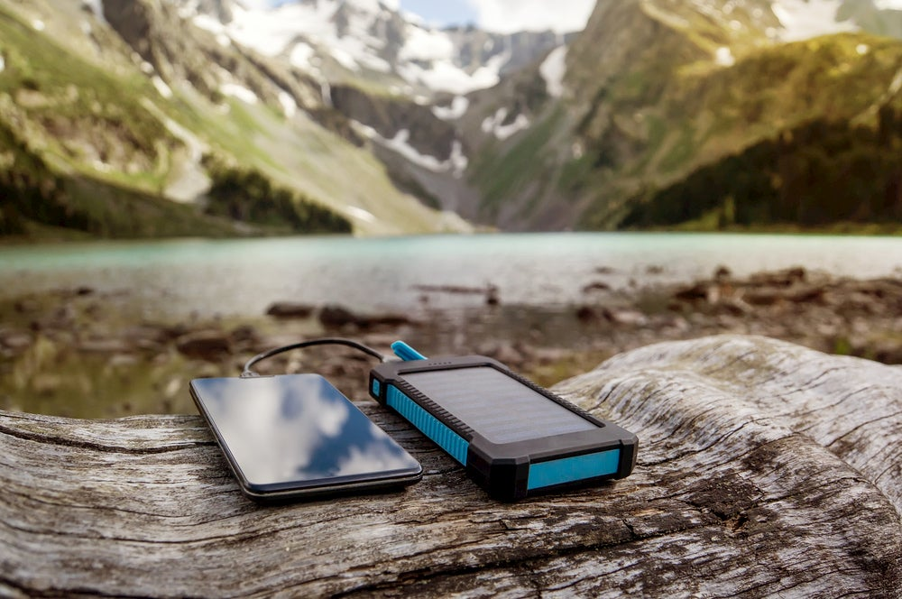 Phone and charger resting on a log with mountain scenery in background