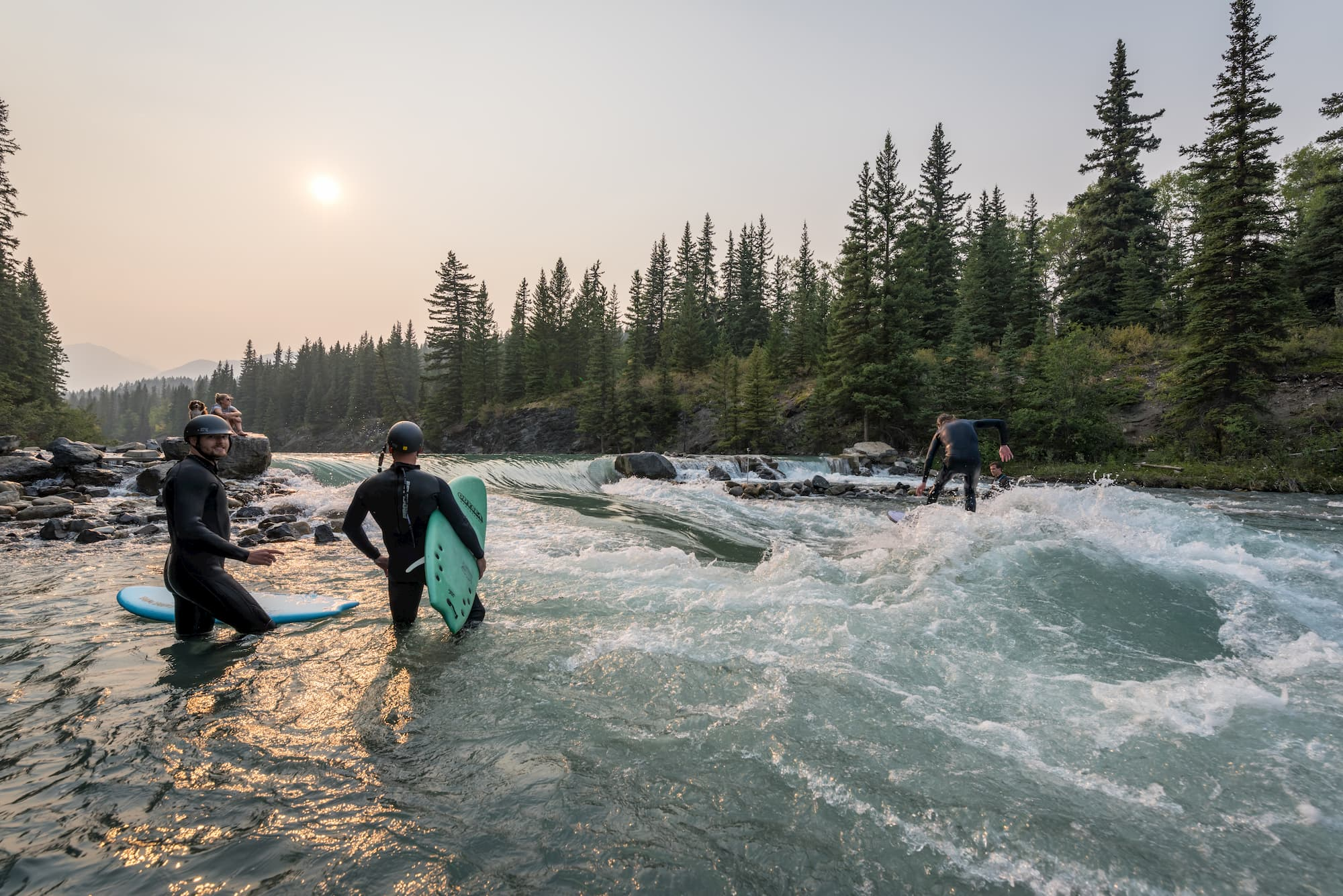 River surfers looking upon person riding the wave.