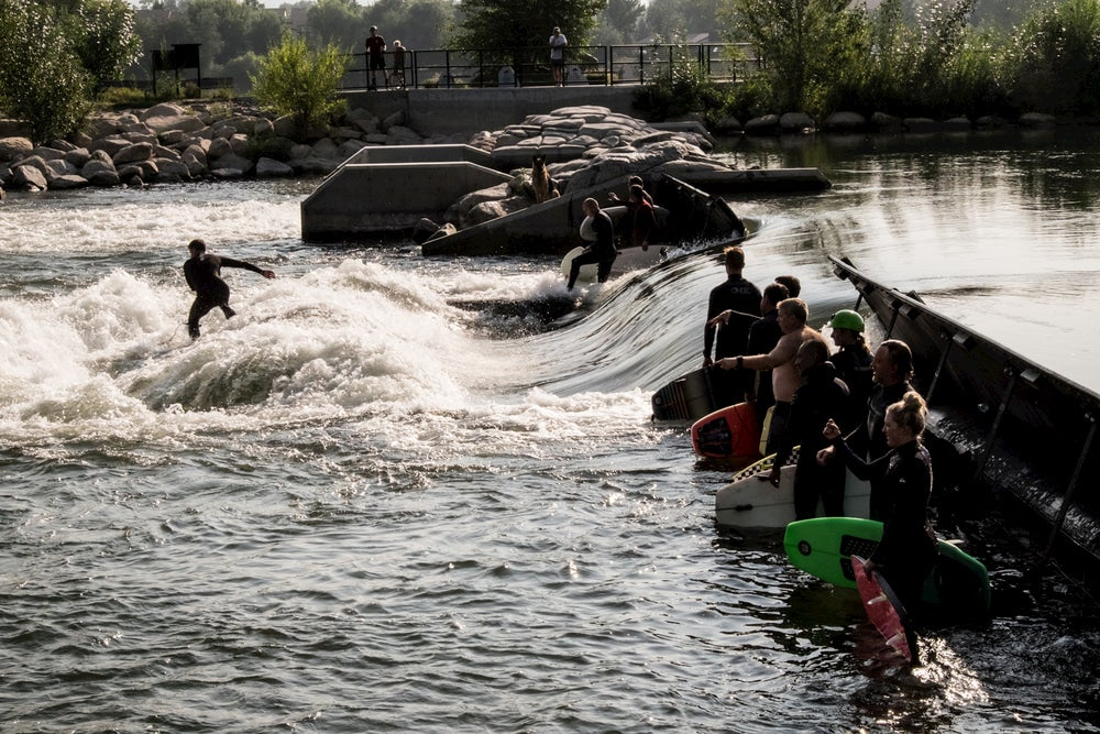 Group of surfers riding a wave in a river in Idaho
