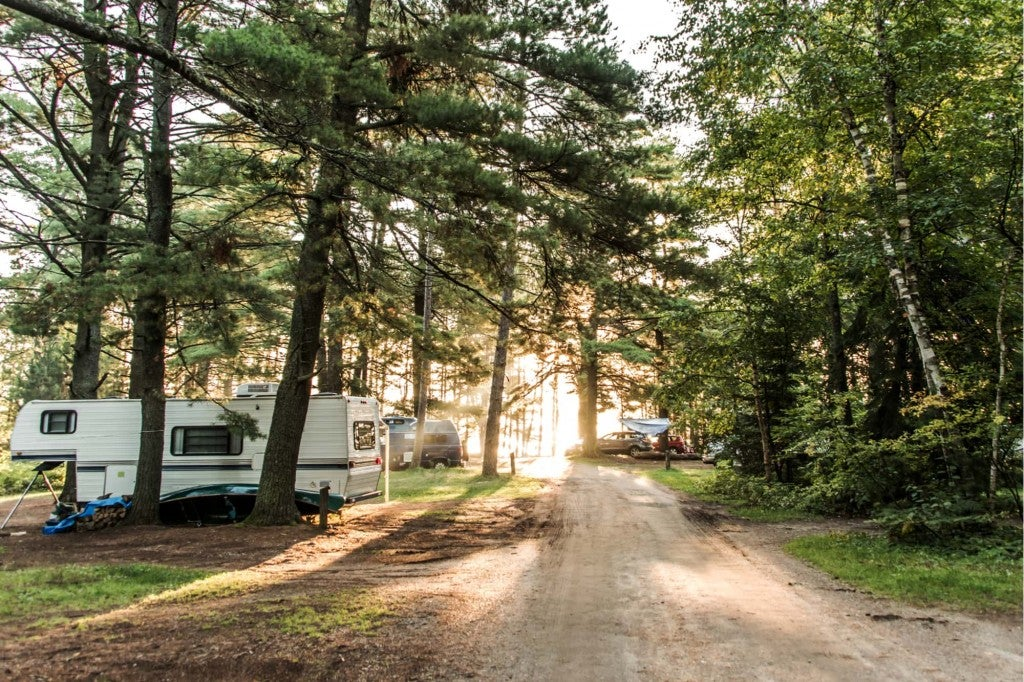 a forested rv campground with a stationary rv and other cars in the sites between trees