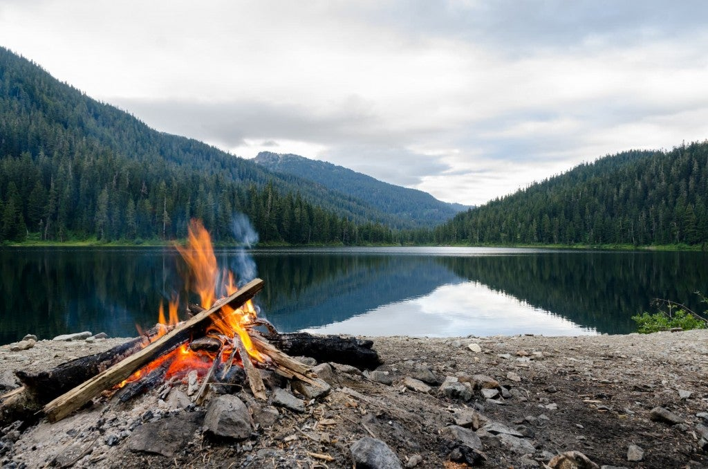 a campfire set up on the shore of a lake