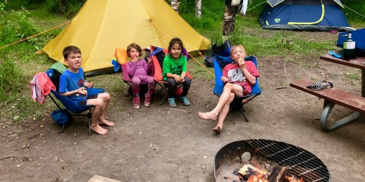 kids gathered around a fire at a campsite in front of a tent