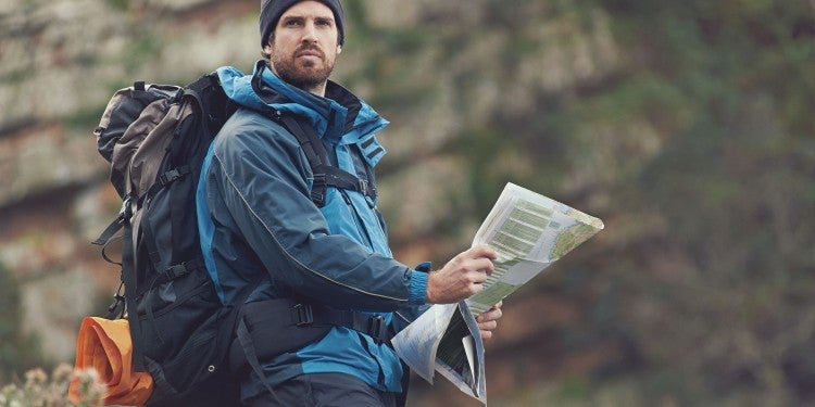a man holding a paper map in the woods while hiking, looking confused
