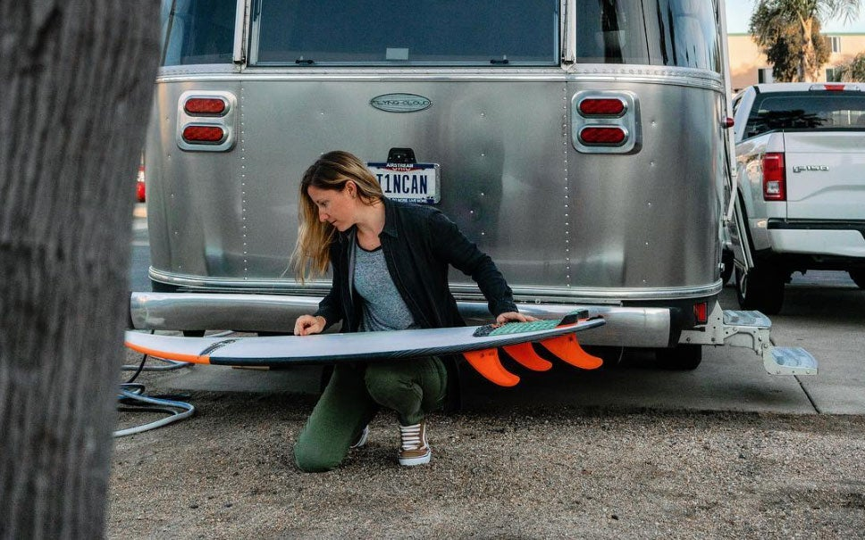 a woman polishes her surfboard in front of an RV