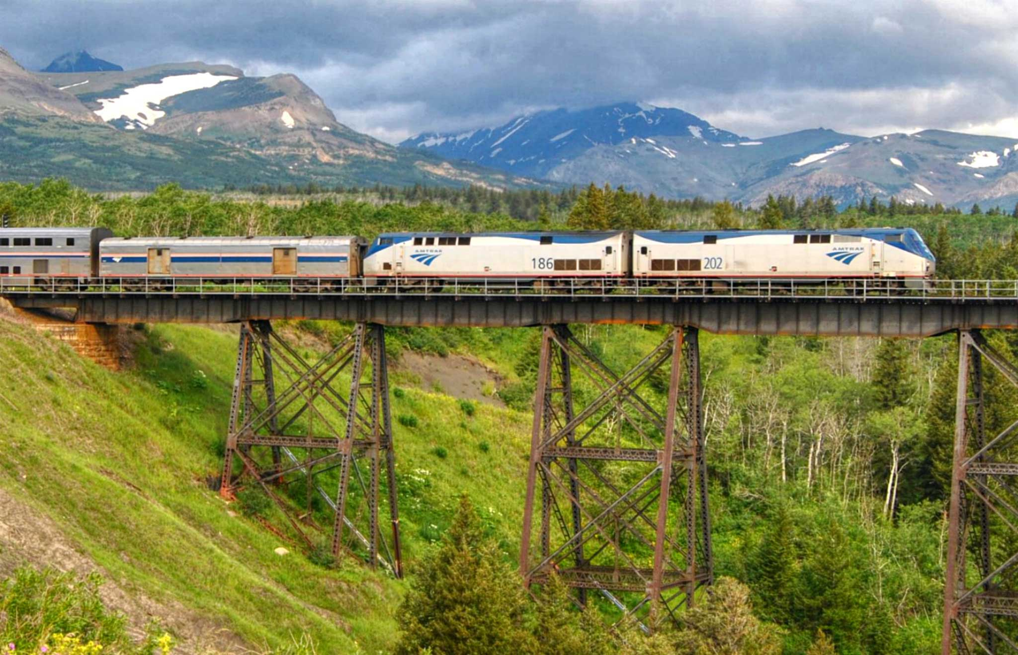 view of train to glacier in the distance as it crosses elevated bridge over green valley