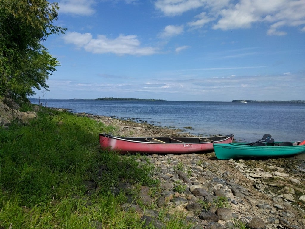 two canoes resting on the rocky shore of lake champlain