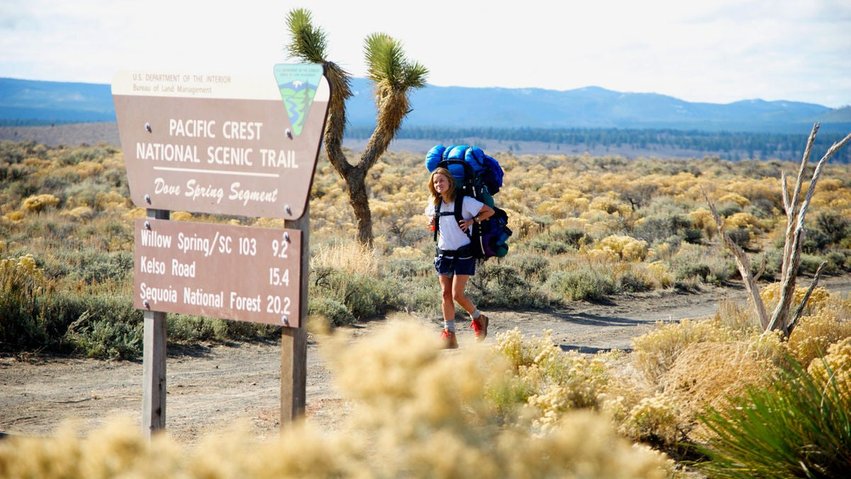 a woman hiking on the pacific crest trail near a sign