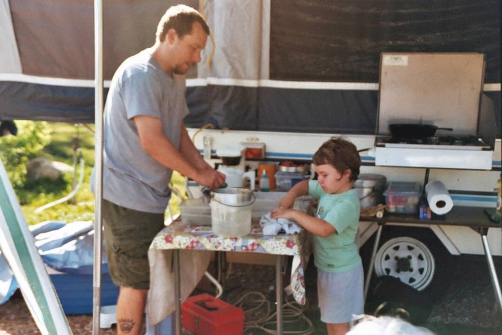 Child and dad cooking with camper in background