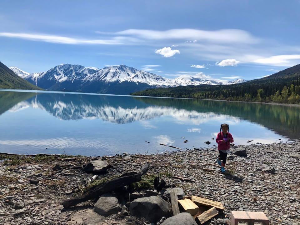 a young child walking along a lake