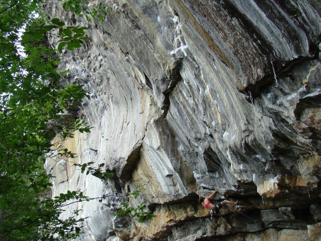 a woman climbing an inverted rock wall