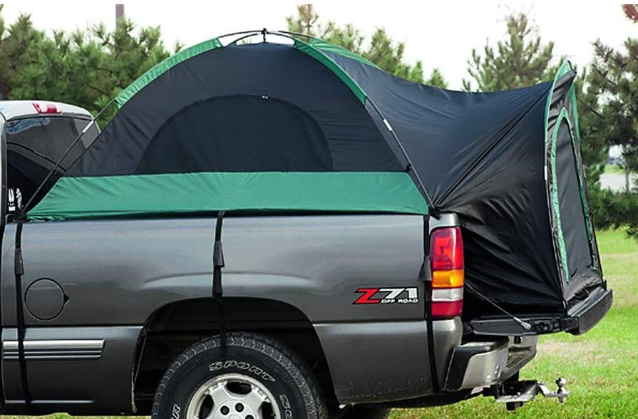 a truck bed tent attached to a pickup truck outdoors