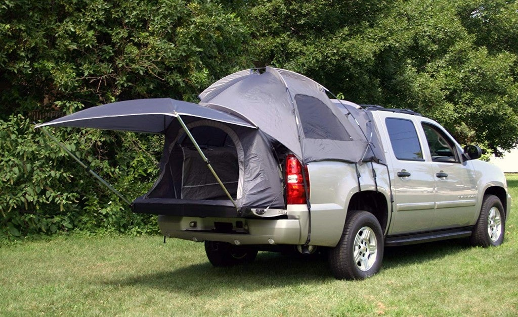 a set up truck bed tent with a sun shade hanging out the back outdoors