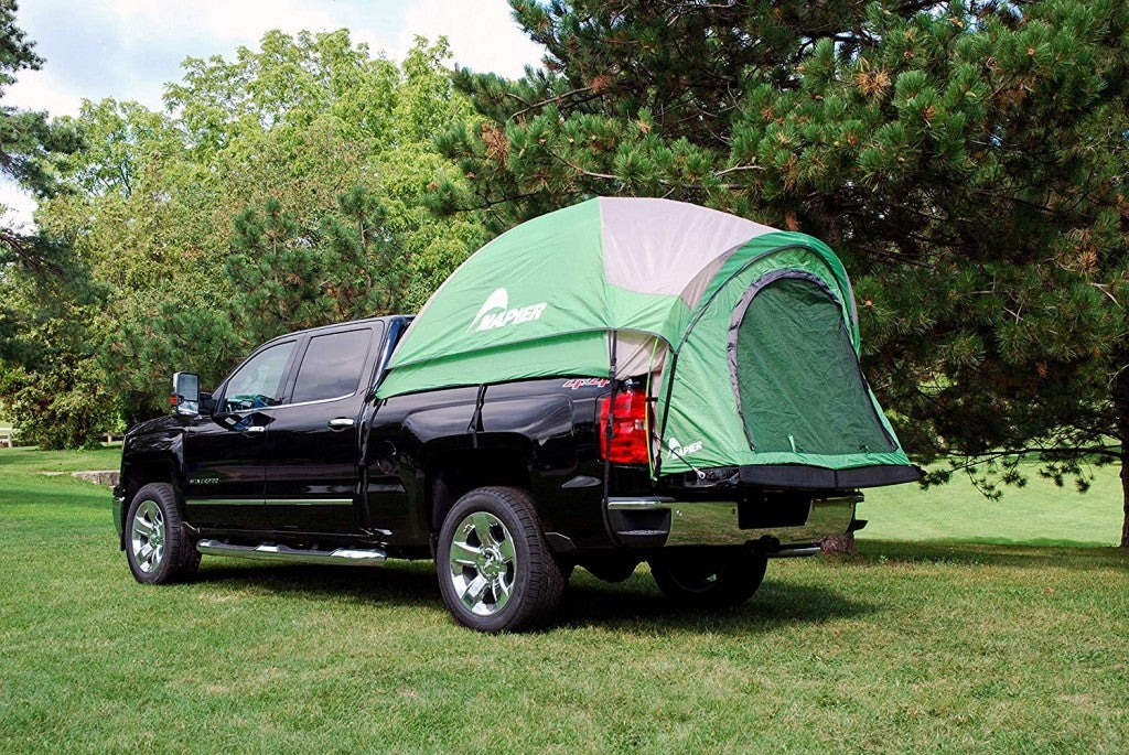 a green truck bet tent hooked up in a park
