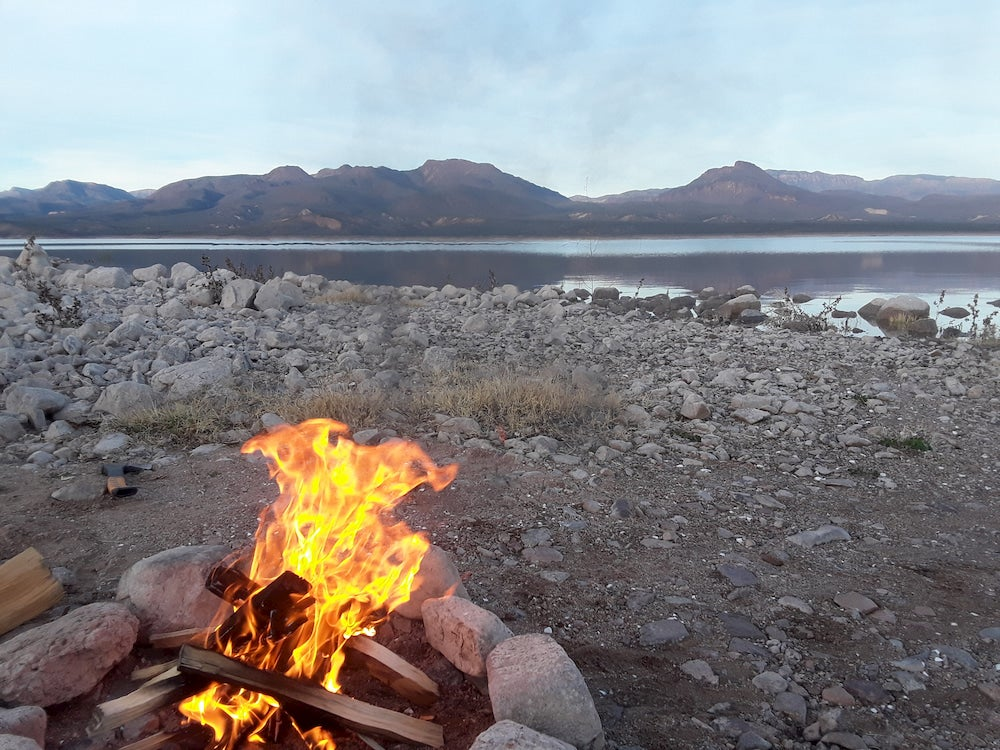 Fire in foreground with lake and mountains in background