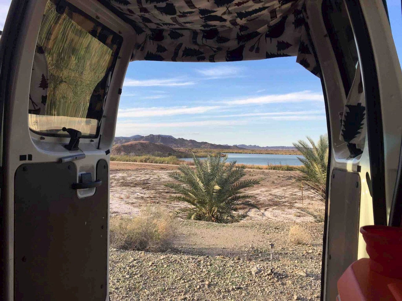 View through camper of tropical plants, desert, and lake.