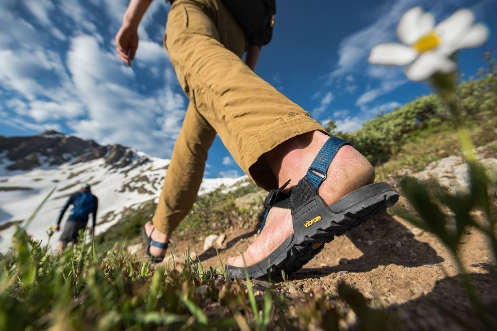 a person walks on a trail in a pair of bedrock hiking sandals