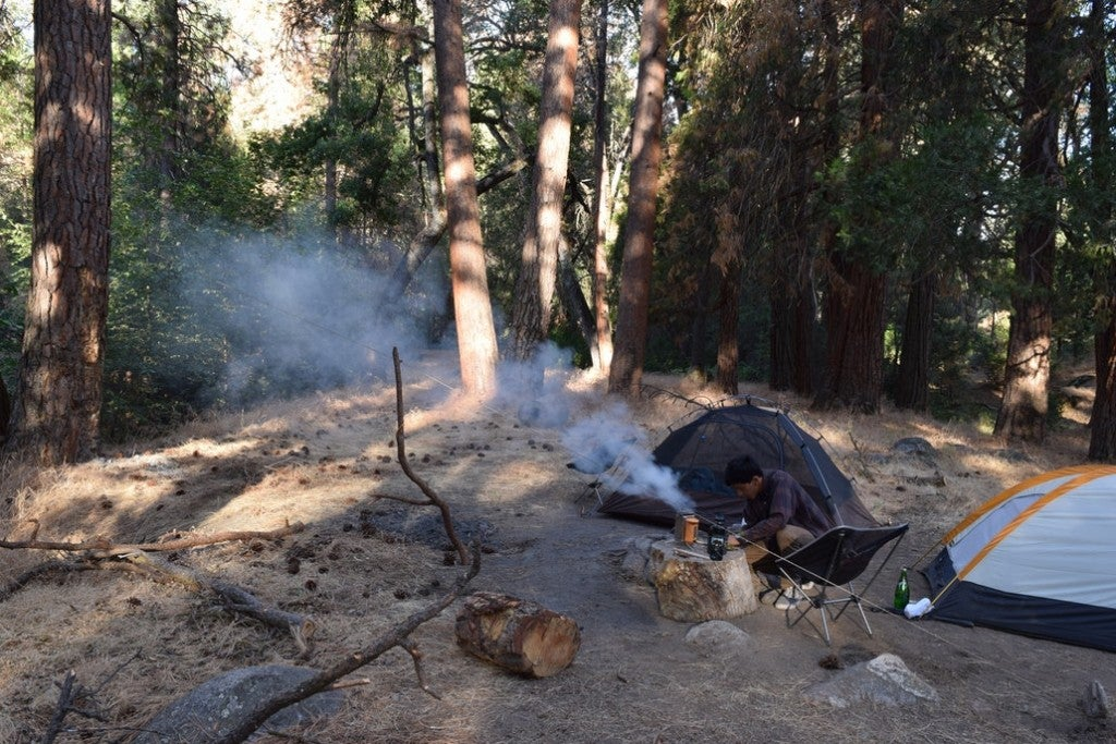 a campsite in the woods with a tent and a man cooking over a fire