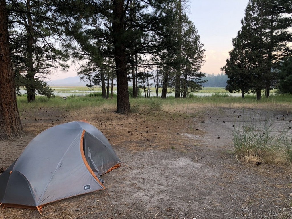 a grey tent set up on a free camping site in california near a lake
