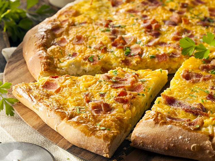close up of a slice of breakfast pizza featuring eggs and bacon on crust