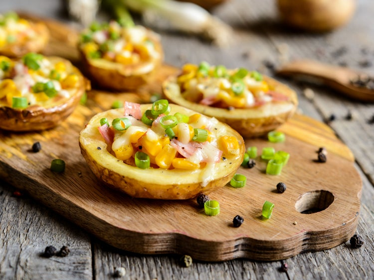 potato halves covered in breakfast ingredients like ham and scallions on a wooden serving tray