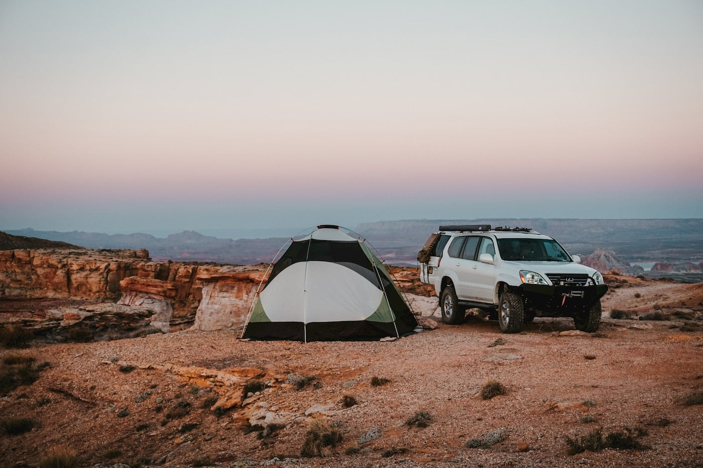 Tent pitched next to car parked in desert backcountry.