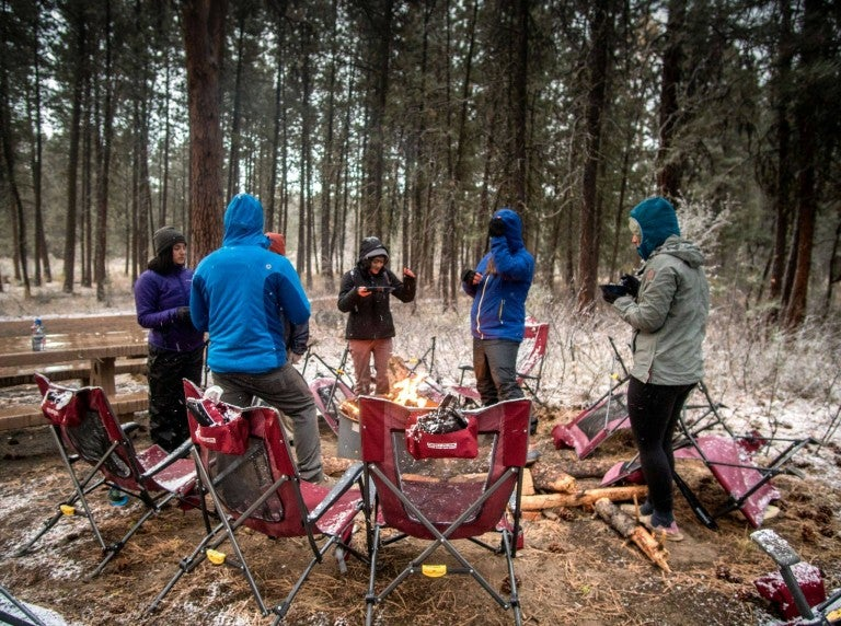a group of campers in jackets around a campfire with camping chairs in a circle