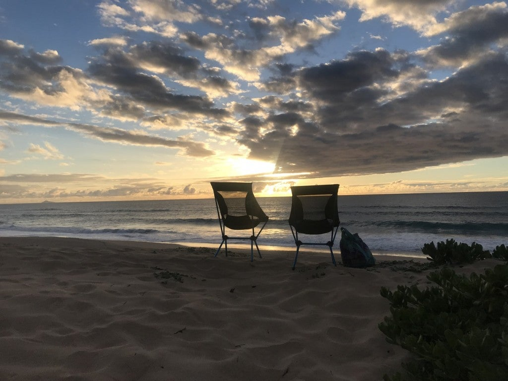two empty camp chairs face ocean as sunset peeks through clouds overhead