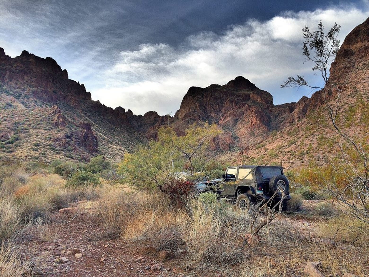 Jeep parked in backcountry brush of Arizona in front of rock cliffs.