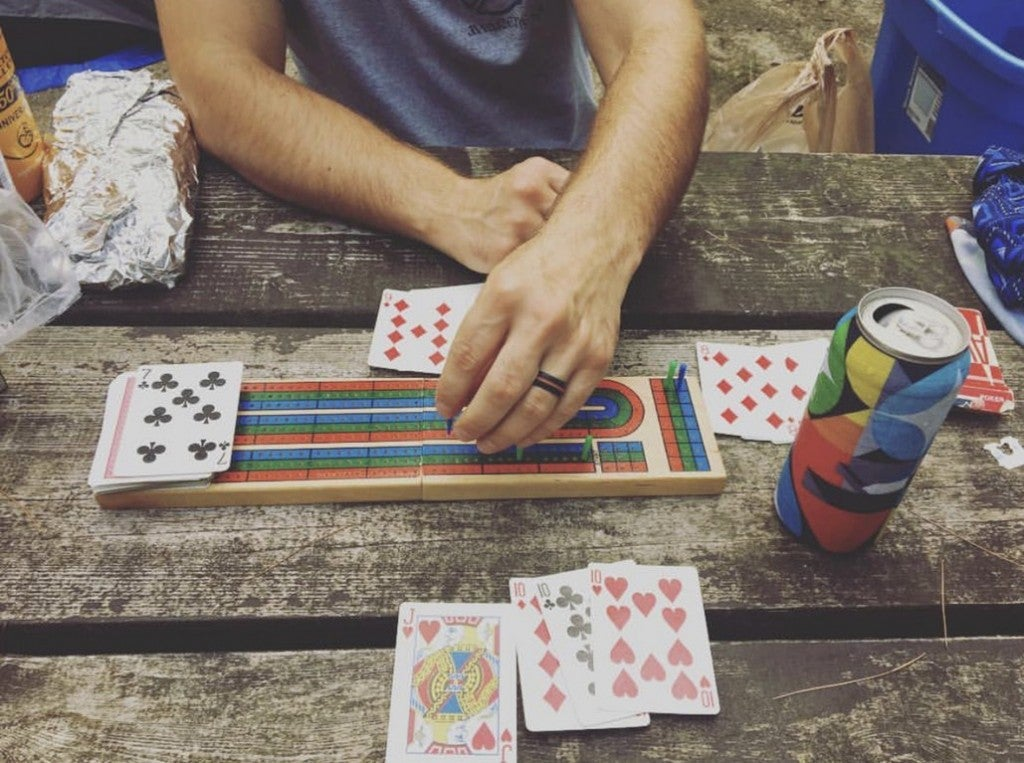 a group of people playing a board game at a campground