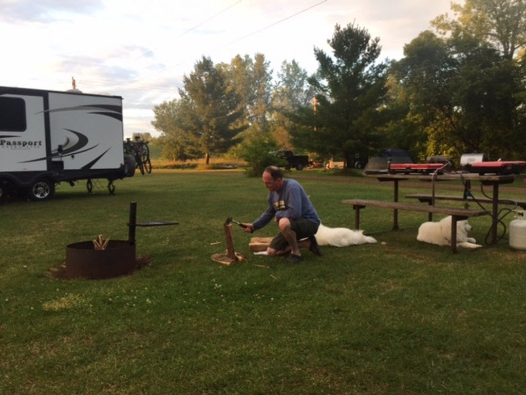 a man at a campground with two dogs cutting wood
