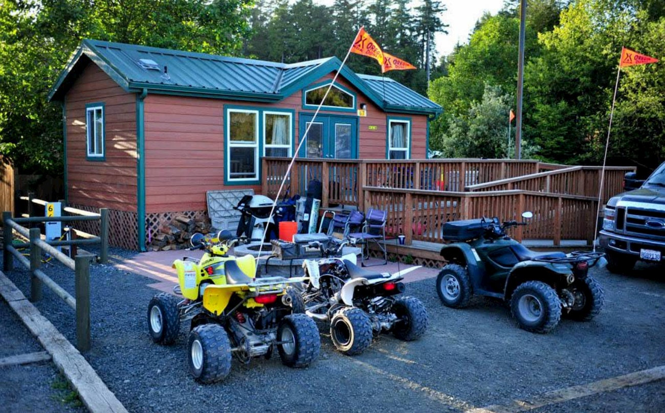 4x4s parked outside of a log campground building.