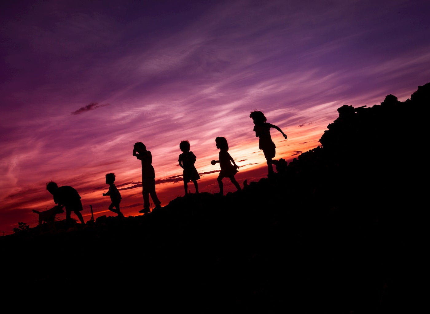 Silhouette of kids running downhill at sunset.