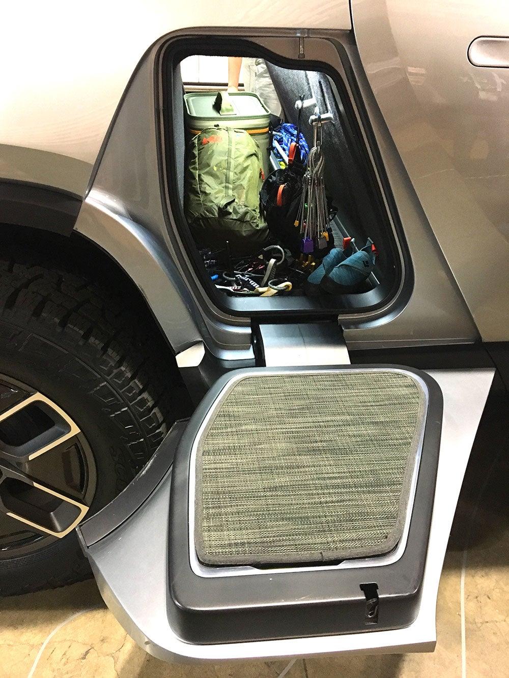 Gear storage tunnel beneath backseats of the Rivian electric truck