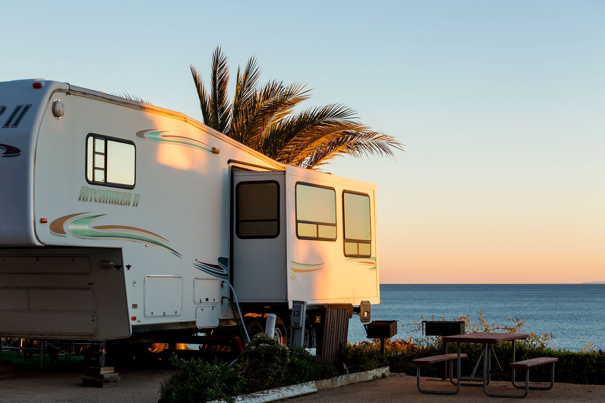 rv set up in beach campsite as the sun sets over the water