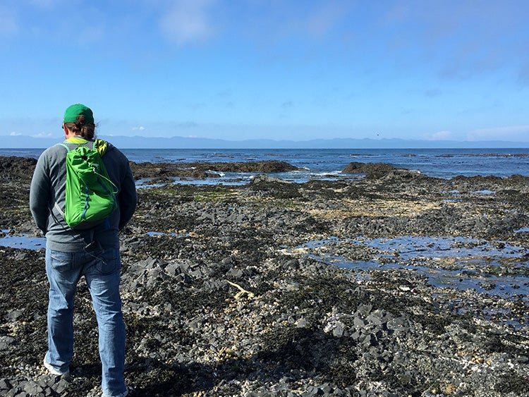 hiker walks near tide pools in salt creek recreation area washington