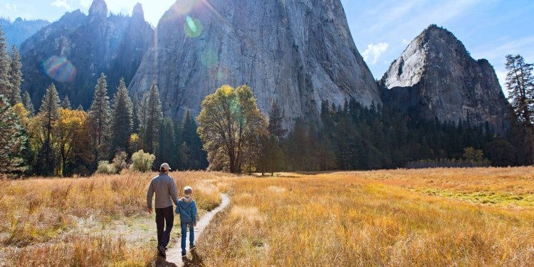 Father and son walking on path with rock face in background