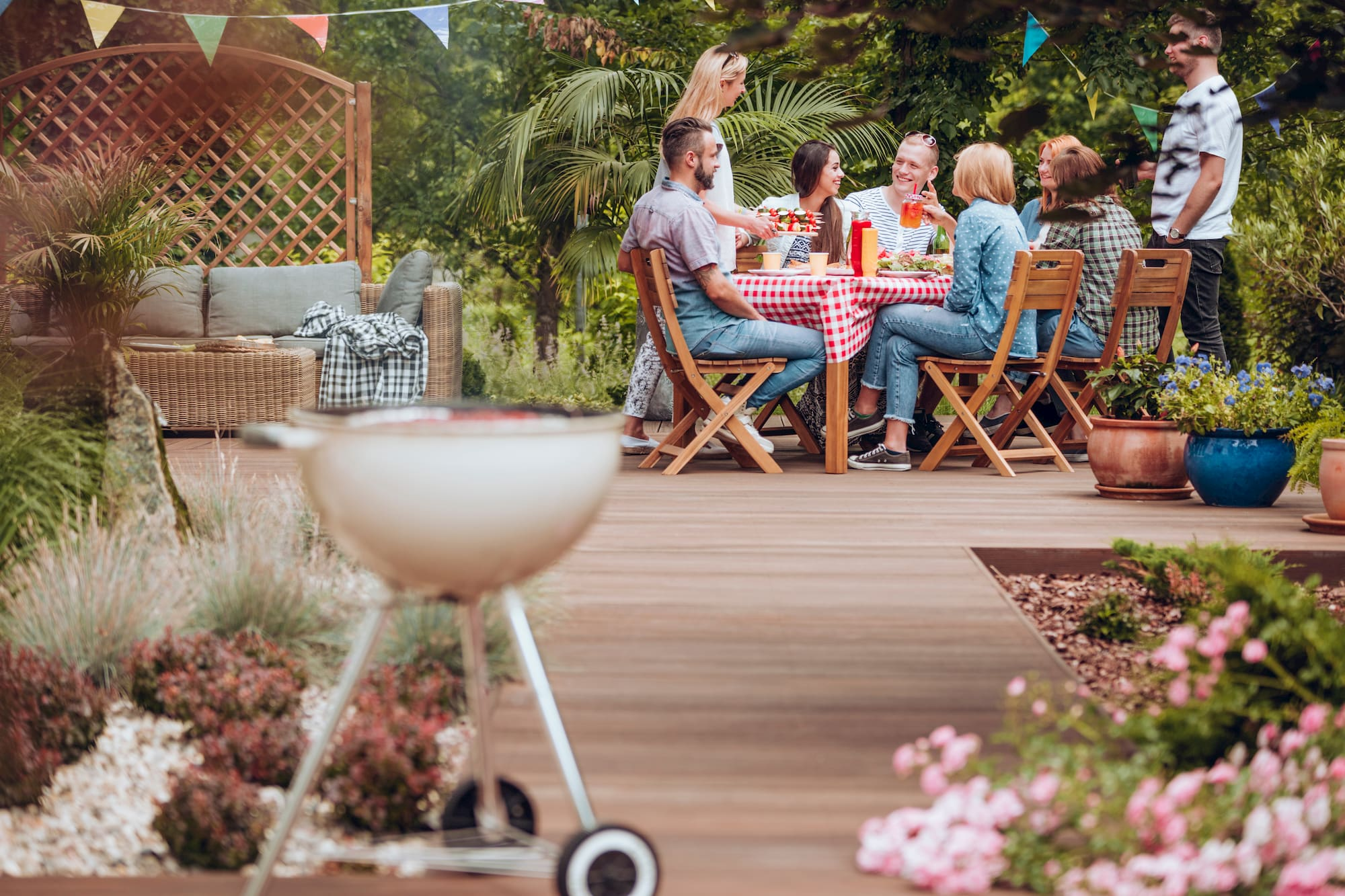 Friends sitting at table in backyard with barbecue in foreground