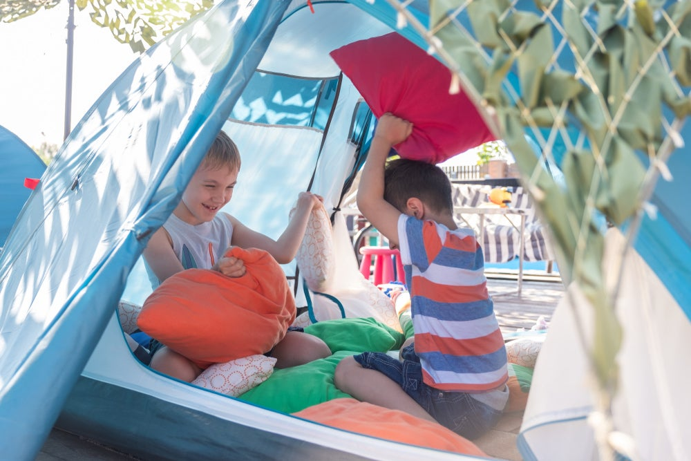 two kids playing in a tent in the daytime
