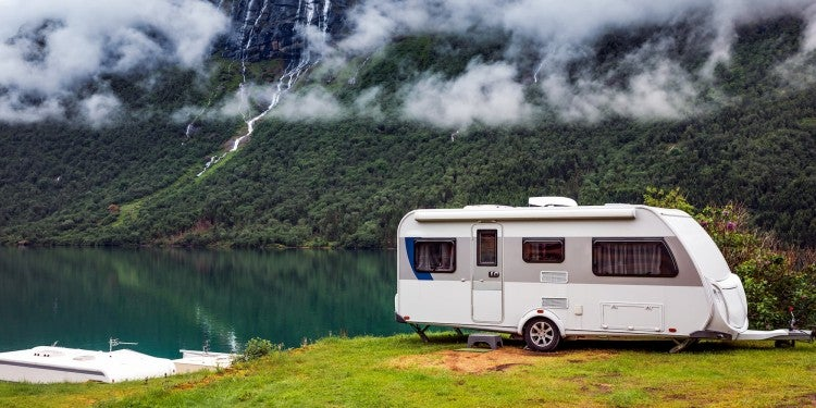 RV next to lake with hill and waterfall in background
