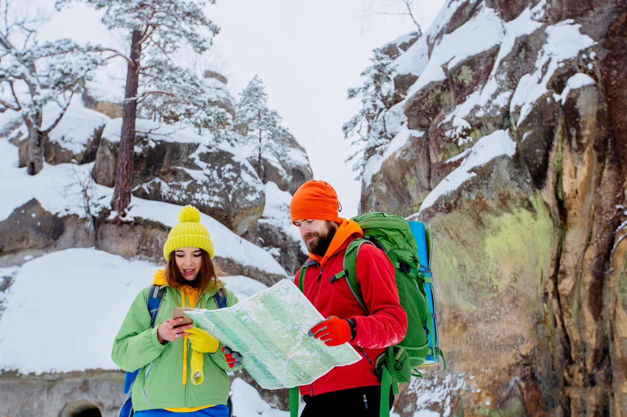 Couple reading a map while hiking in the winter.