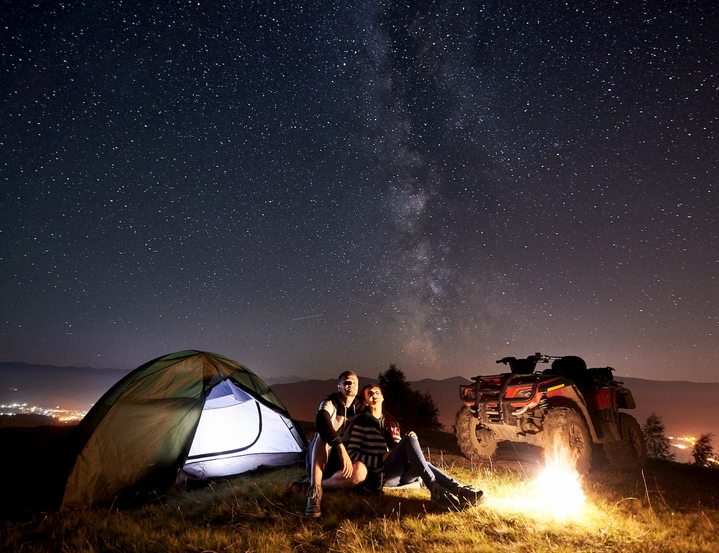 Couple hanging out by the fire beside a tent and 4x4.