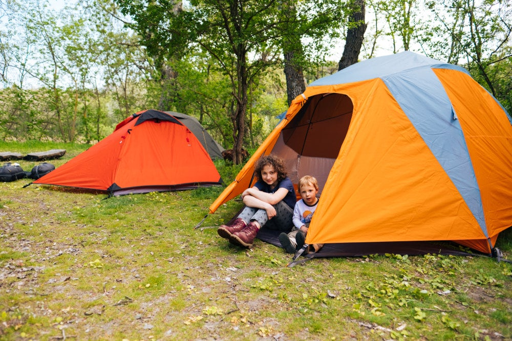 two young children playing in a tent near a second tent at a campground