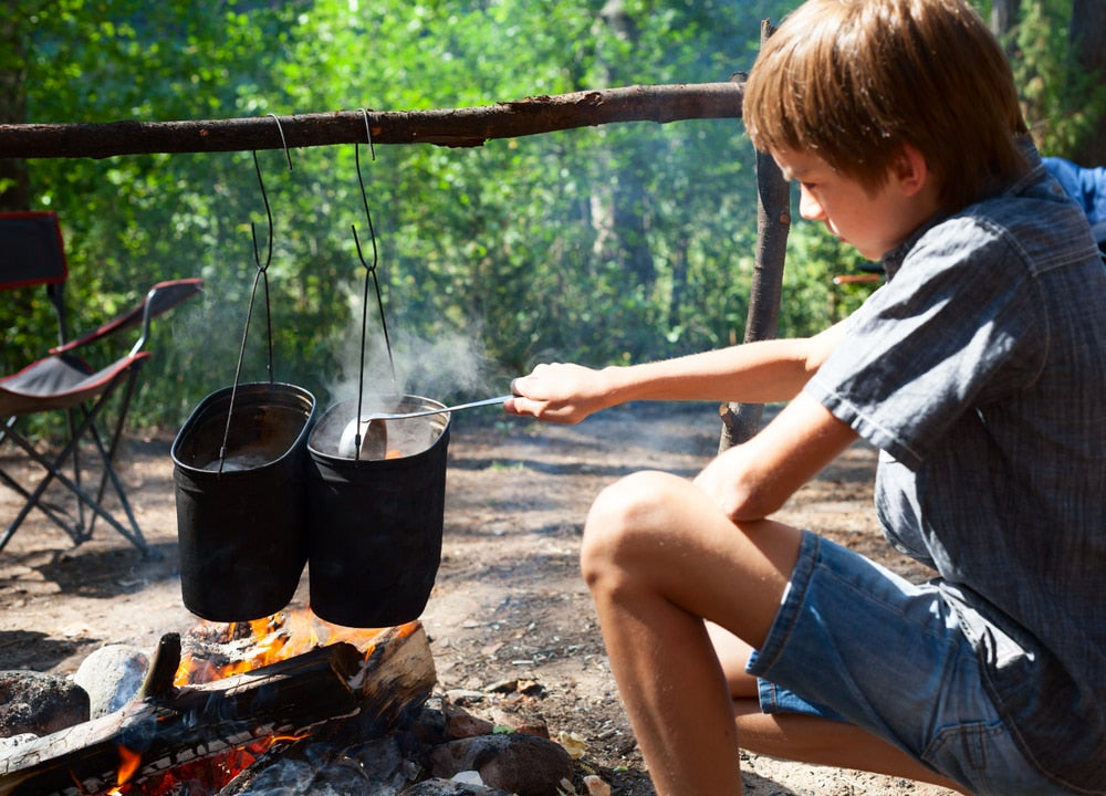 a kid cooking over a campfire at a campground