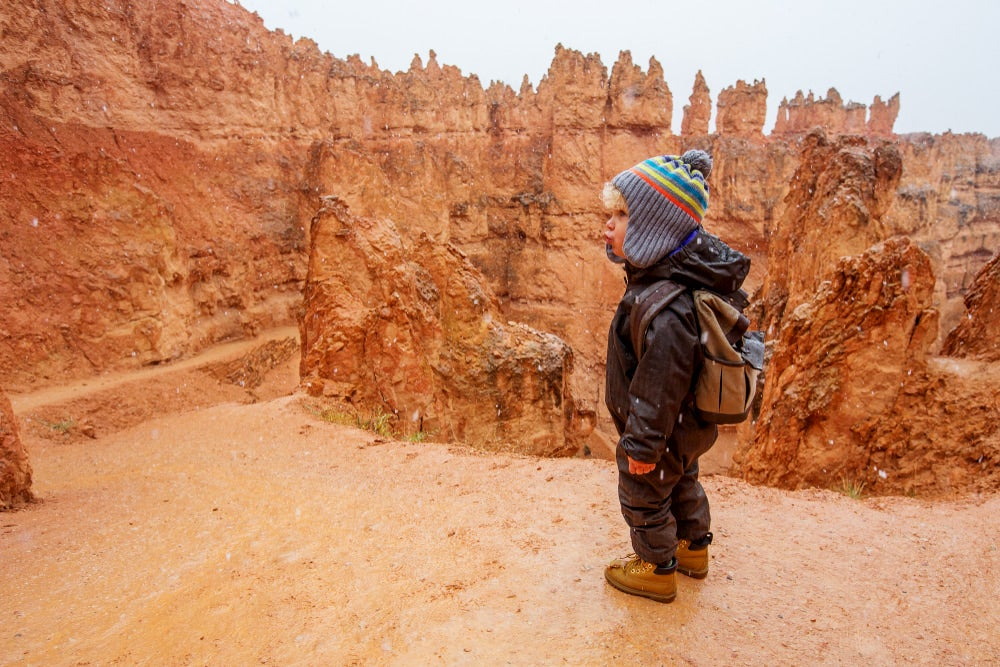 Child standing with red rocks behind him