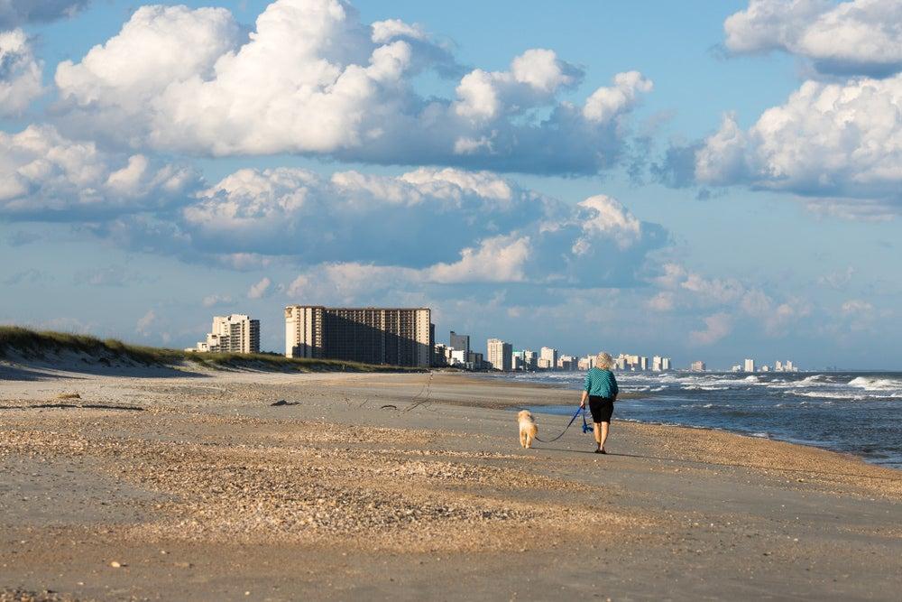 a woman walking a dog on myrtle beach in south carolina